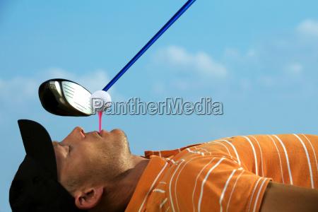 man balancing golf ball on tee