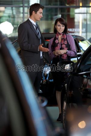 car salesman explaining car features to