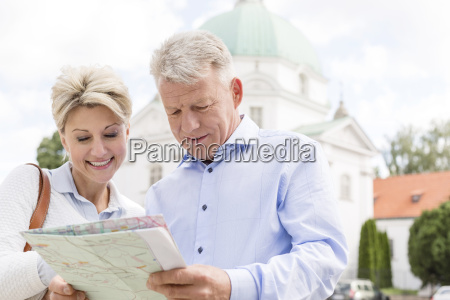 smiling middle aged couple reading map
