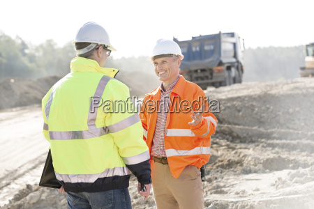 happy engineer talking to colleague at