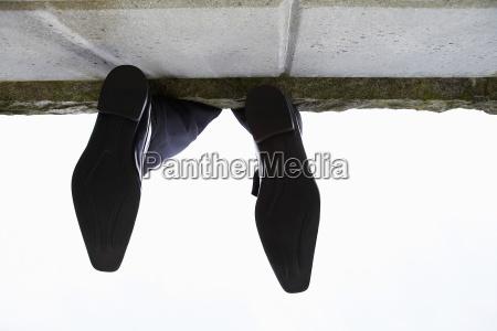 feet dangling over wall low angle