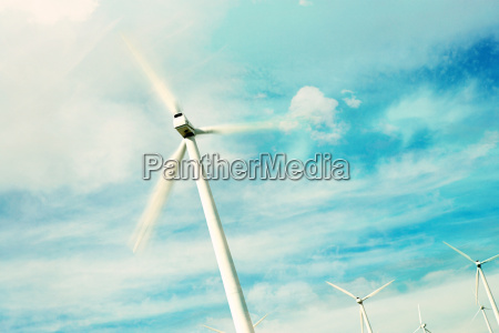 wind turbine against sky with clouds