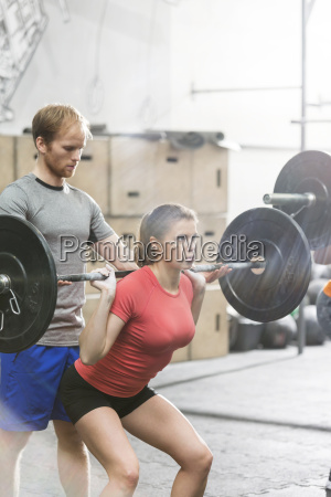 man assisting woman in lifting barbell
