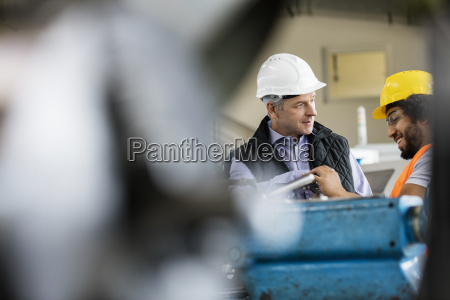 mature male supervisor talking with worker