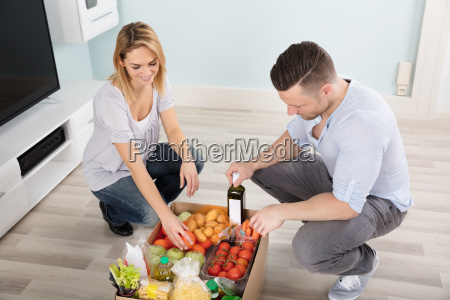 couple looking at groceries in the