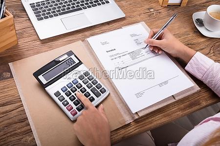 businesswoman calculating tax on desk
