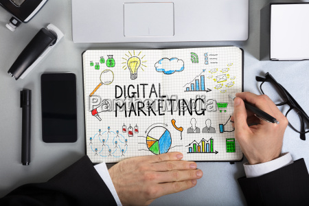 businessperson drawing digital marketing on notebook