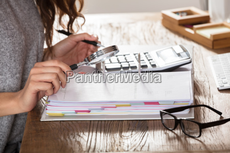 auditor looking invoice through magnifying glass