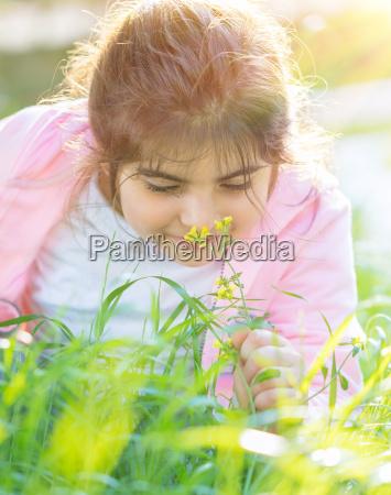 little girl enjoying flowers