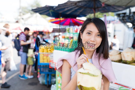 woman enjoy coconut juciy in street