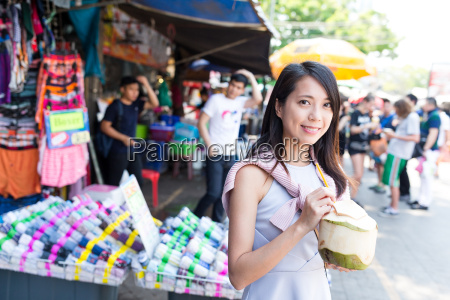 woman having coconut drink in street