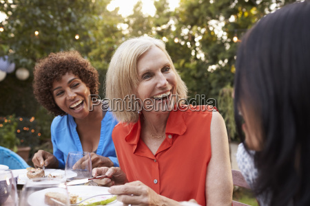 mature female friends enjoying outdoor meal