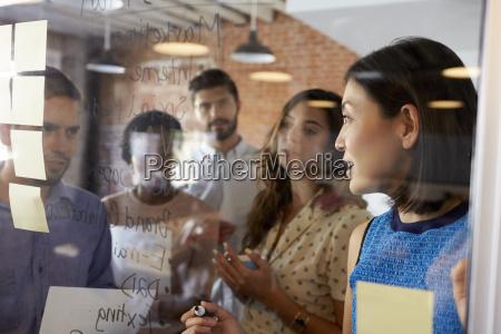 businesswoman writing ideas on glass screen