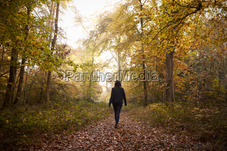 woman walking along path in autumn