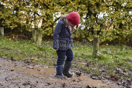 girl splashing in puddle on winter