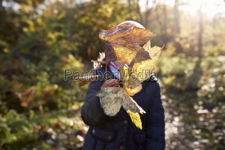 young girl playing with leaves on
