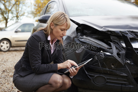 loss adjuster with digital tablet inspecting