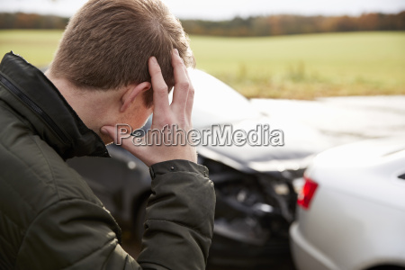 frustrated man with damaged car after