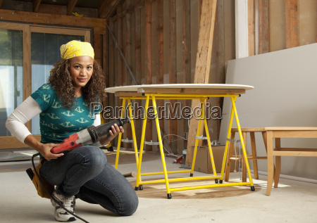 hispanic woman holding power tool