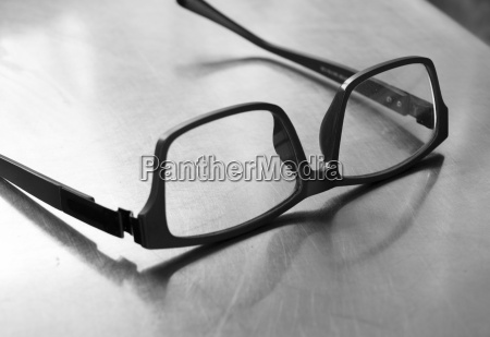plastic frame glasses on steel table