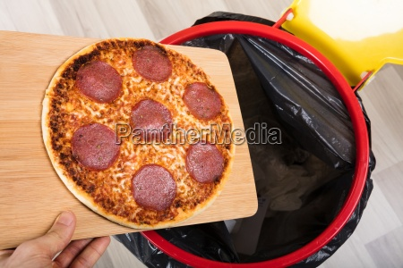 person throwing salami pizza in dustbin