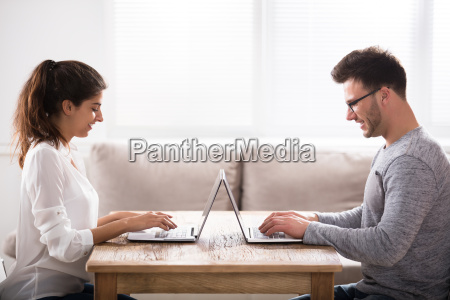 online dating concept couple using laptops