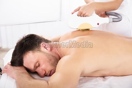 man having laser treatment at beauty