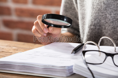 businesswoman looking at document through magnifying