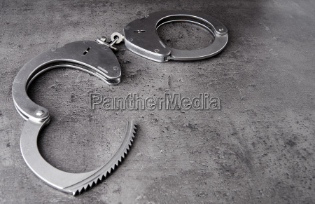 opened police handcuffs on rough grey