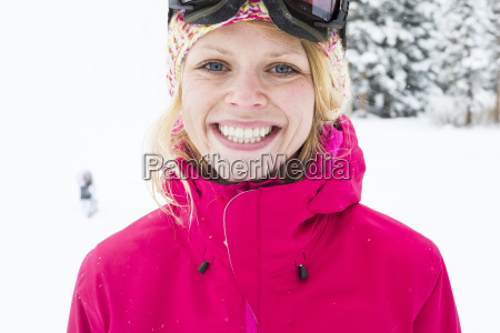 young woman with bright smile skiing