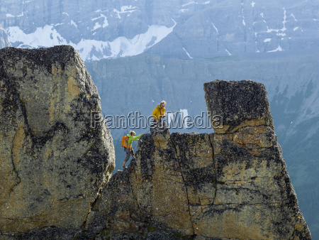 mountaineering couple ascend rock pinnacle mountains