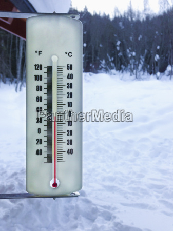thermometer below freezing in snowy landscape