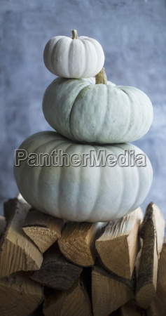three pumpkins stacked on firewood