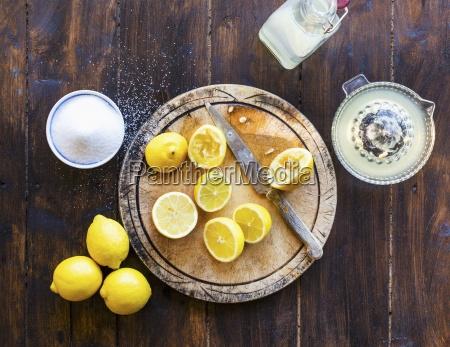 squeezing fresh lemons with sugar bottle