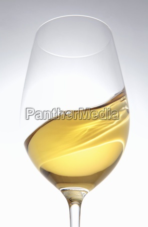 a glass of white wine being