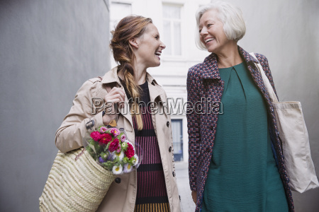 smiling mother and daughter with shopping