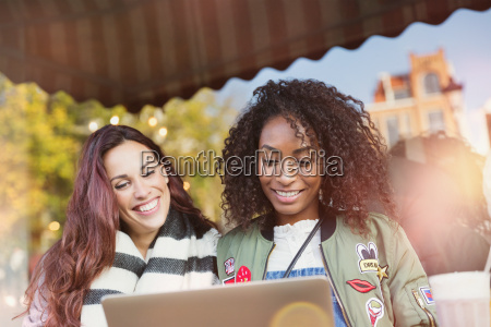 smiling young women friends using laptop