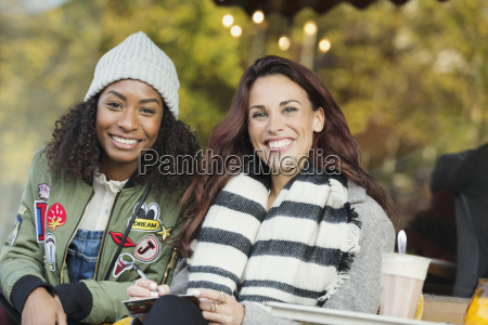 portrait smiling young women friends writing