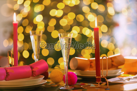 champagne flutes candles and christmas crackers