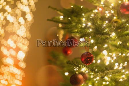 red ornaments hanging from christmas tree