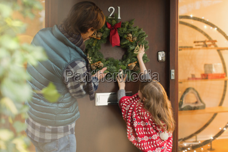 father and daughter hanging christmas wreath