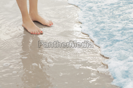 womans feet standing in surf at