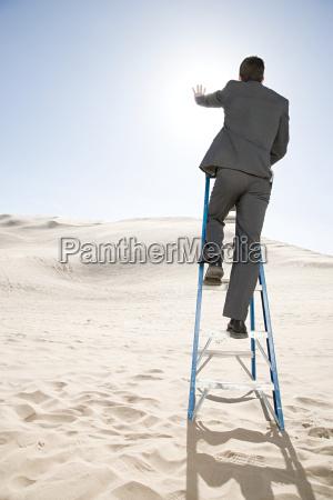 man on ladder in the desert