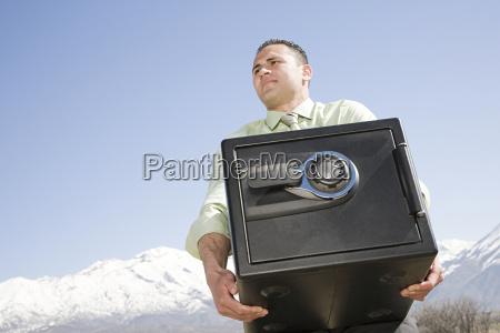 man carrying safe near mountains