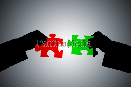 silhouette of hands assembling jigsaw puzzle