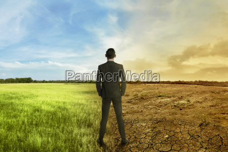 asian businessman standing between different climate