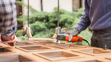 carpenter at work with angular sander