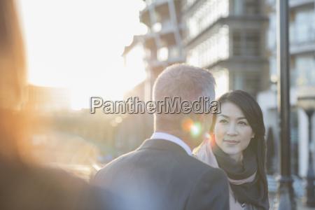 businesswoman listening to businessman on urban