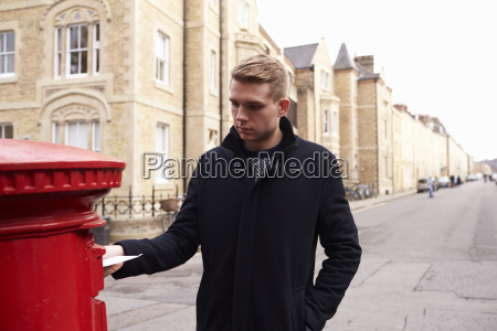 man posting letter in red british