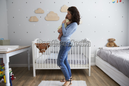 mother holding newborn baby son in